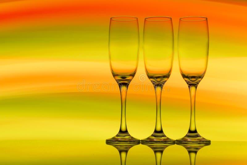 Trzy szampańskiego szkła z tęczą kolorowy lekki obraz za one z rzędu obrazy stock