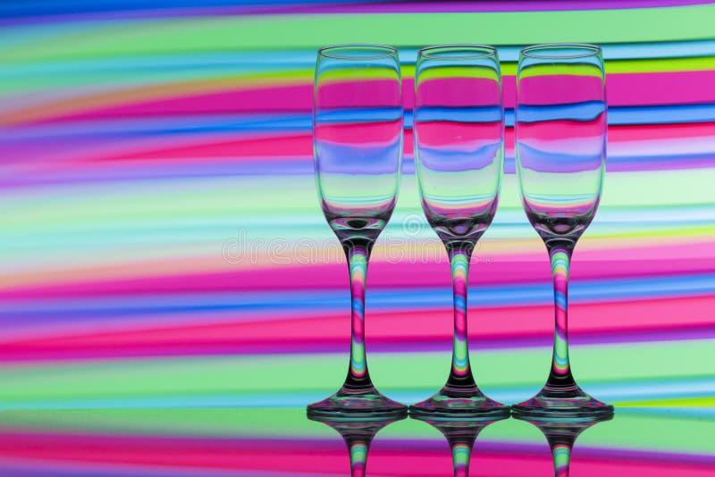 Trzy szampańskiego szkła z tęczą kolorowy lekki obraz za one z rzędu zdjęcia stock