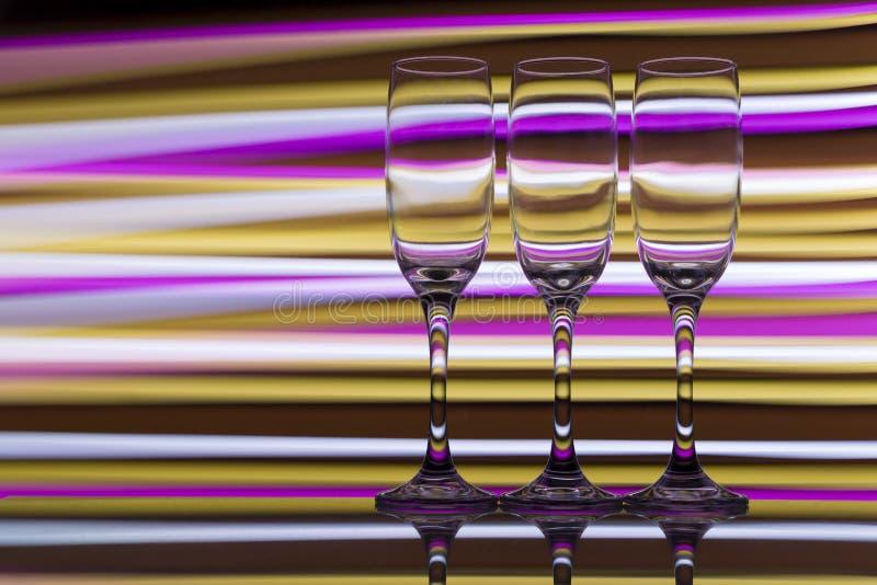 Trzy szampańskiego szkła z tęczą kolorowy lekki obraz za one z rzędu fotografia stock