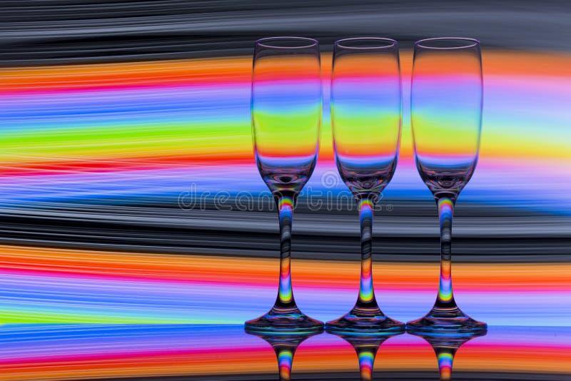 Trzy szampańskiego szkła z tęczą kolorowy lekki obraz za one z rzędu zdjęcie stock