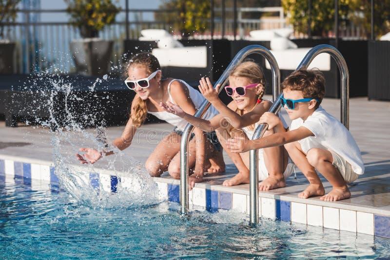 Trzy szczęśliwego dziecka siedzi blisko pływackiego basenu przy dnia czasem fotografia stock