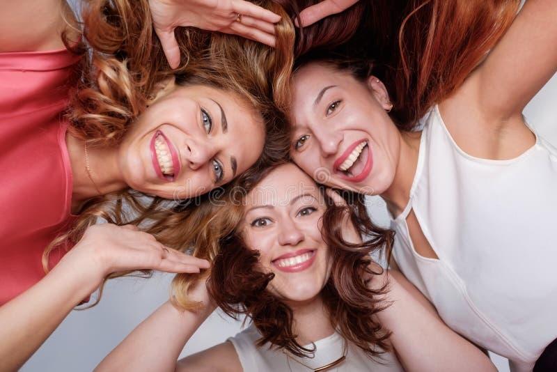 Trzy szczęśliwego kobieta przyjaciela patrzeje w dół zdjęcia stock