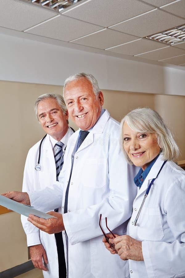 Trzy szczęśliwego lekarza w szpitalu obraz stock