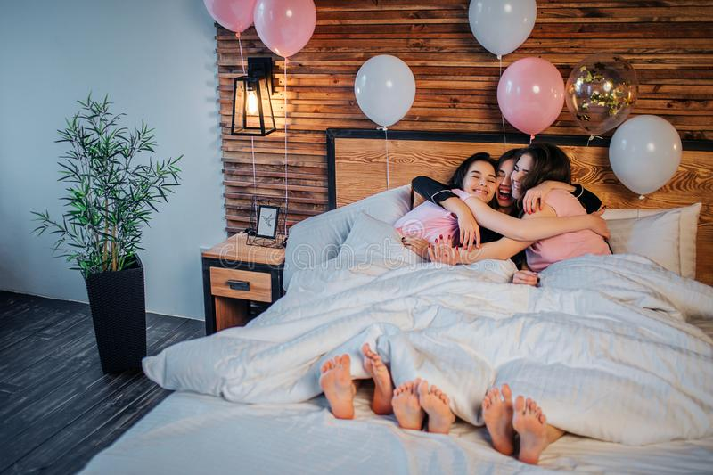 Trzy szczęśliwego modela kłama pod białą koc i obejmować wpólnie One uśmiechają się Dziewczyny odzieży piżamy Baloons jest przy ł obrazy royalty free