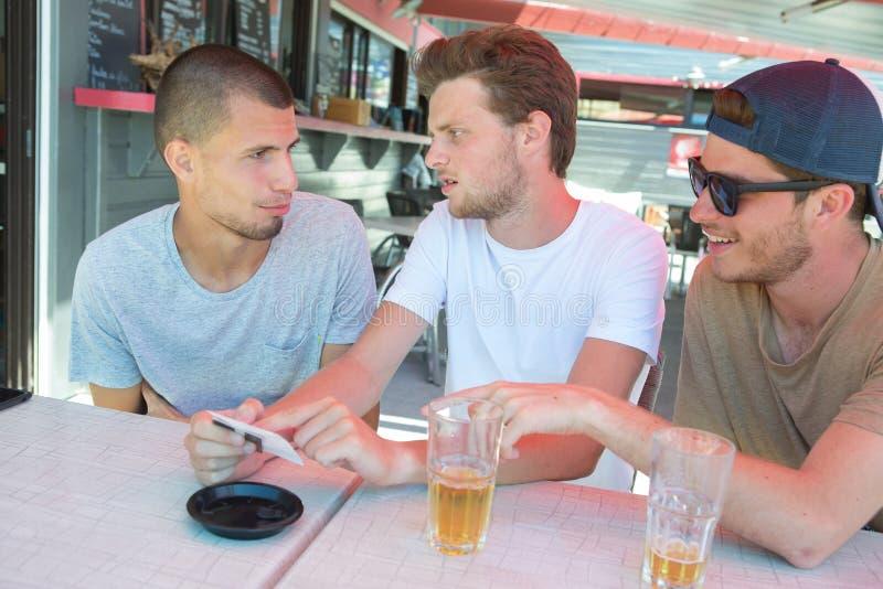 Trzy szczęśliwego przyjaciela opowiada i śmia się w kawa tarasie obrazy stock
