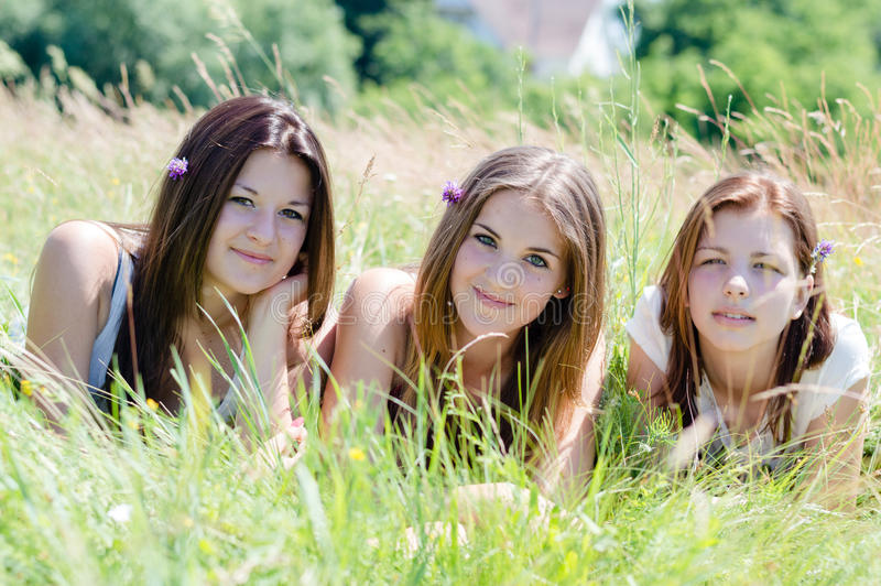 Trzy szczęśliwego uśmiechniętego & patrzeją kamer młodych kobiet przyjaciela kłama w wysokiej zielonej trawie zdjęcie stock