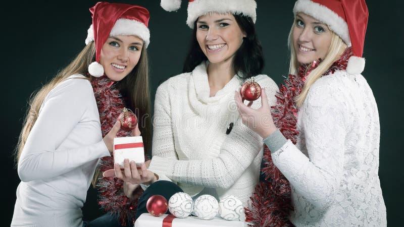 Trzy szczęśliwej młodej dziewczyny ubierali jako Święty Mikołaj obsiadanie z bu zdjęcie royalty free