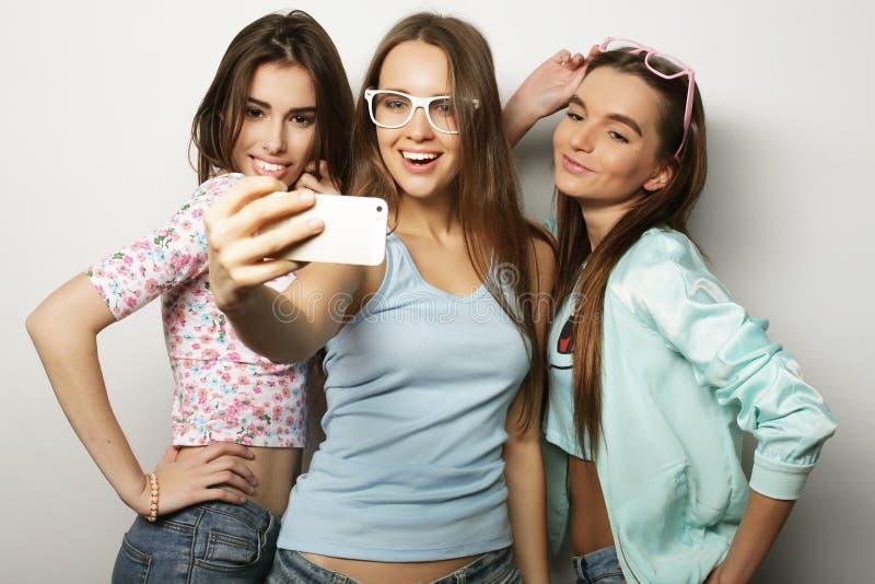 Trzy szczęśliwej nastoletniej dziewczyny z smartphone bierze selfie zdjęcie stock