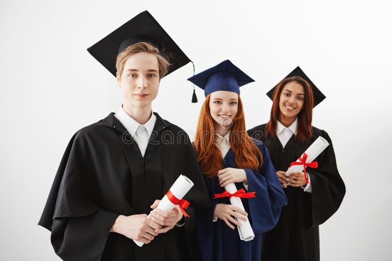 Trzy szczęśliwy międzynarodowy uniwersytet kończy studia uśmiechniętych cieszenia mienia dyplomy nad białym tłem Przyszłościowi p obraz stock