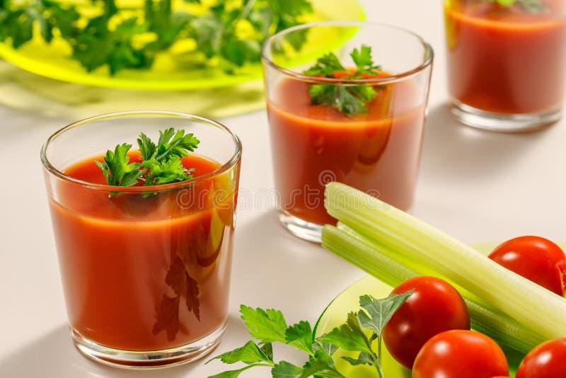 Trzy szkła dekorującego z pietruszki lub kolenderów liśćmi pomidorowy sok Następnie będzie talerz pietruszka, pomidory i selerów  obraz stock