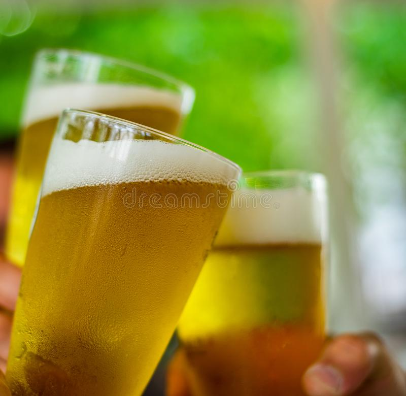 Trzy szkła piwo w ręce Piwni szkła clinking przy plenerowym barem lub pubem obraz royalty free