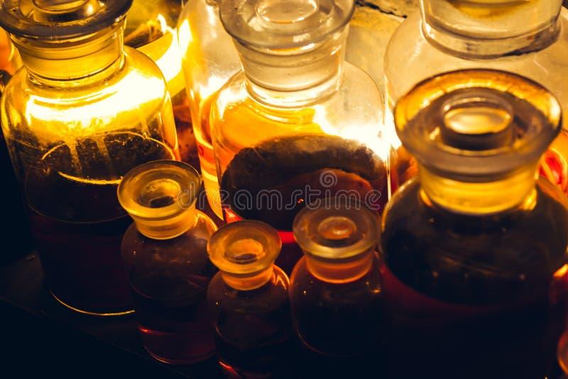 Trzy szklanego zbiornika z kolorowymi szlamowymi ciecza i spadku liśćmi Hallow wigilii guślarstwa magii pojęcie zdjęcia royalty free