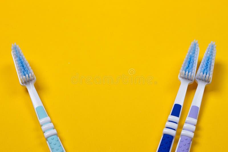 trzy Toothbrushes na żółtym tle zdjęcie stock