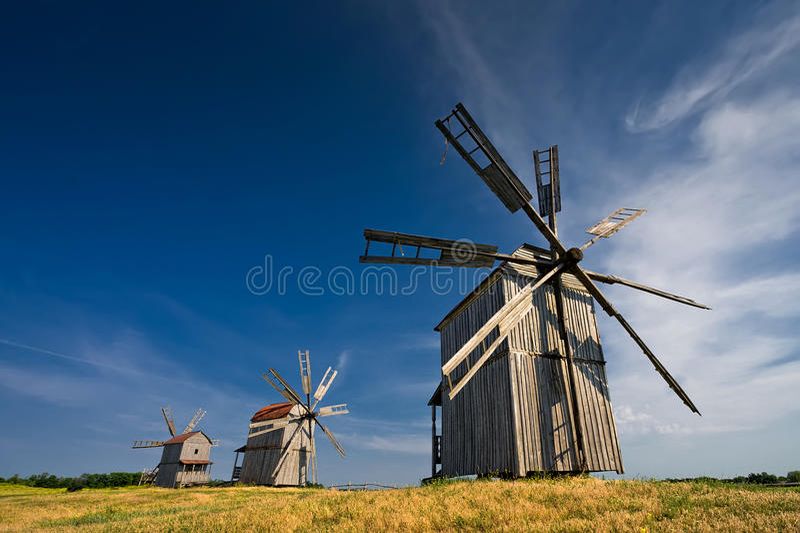 Trzy tradycyjnego wiatraczka na wsi przy zmierzchem obraz stock