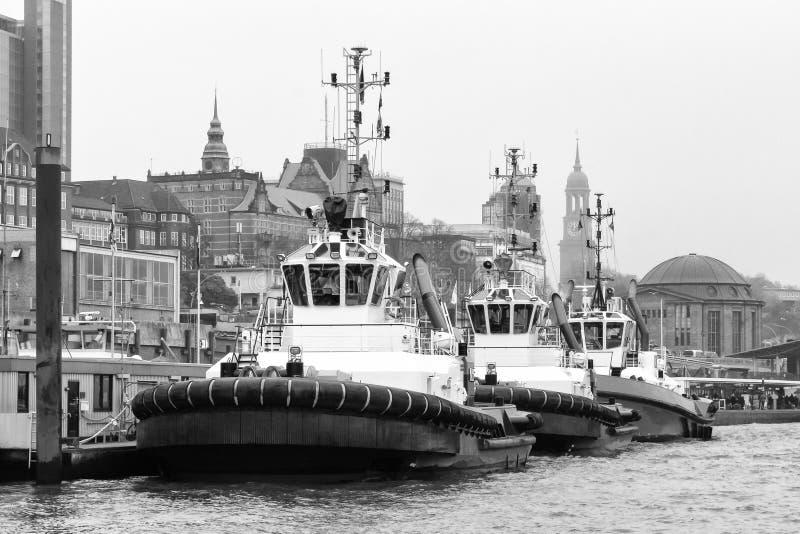 Trzy tugboats przy St Pauli Landungsbrà ¼ cken mola w Hamburg w czarny i biały fotografia royalty free
