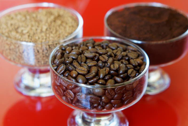 Trzy typu kawa w szklanych pucharach na czerwonym tle: piec fasole, ziemia, chwila zdjęcie stock