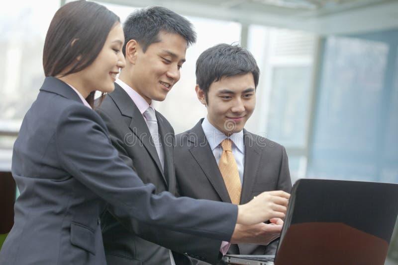 Trzy uśmiechniętego ludzie biznesu patrzeje laptop i wskazuje, indoors zdjęcia stock