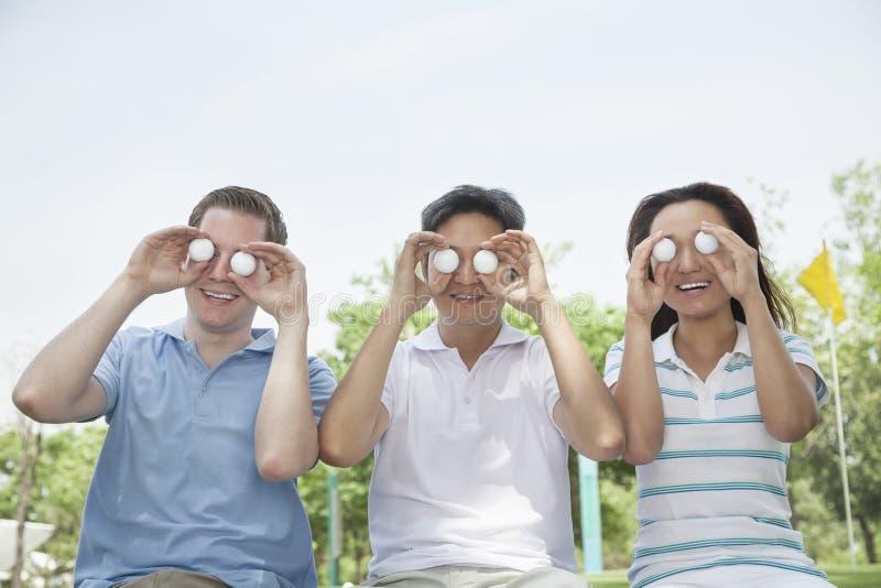 Trzy uśmiechniętego przyjaciela trzyma up piłki golfowe przed ich oczami z rzędu zdjęcie royalty free