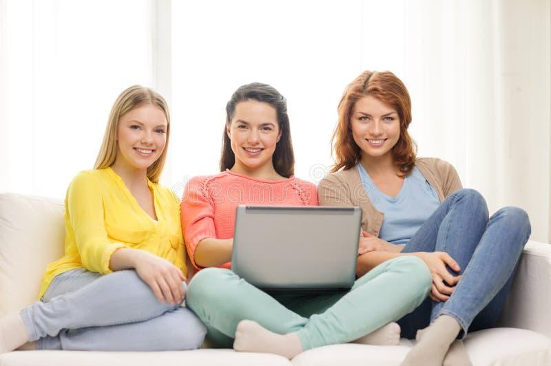 Trzy uśmiechniętej nastoletniej dziewczyny z laptopem w domu fotografia stock