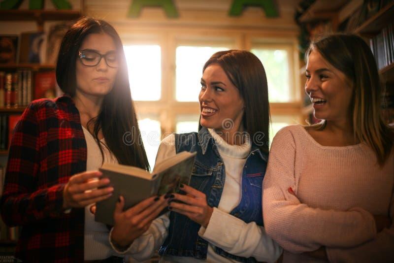 Trzy uśmiechniętej uczeń dziewczyny w bibliotece wpólnie obraz royalty free
