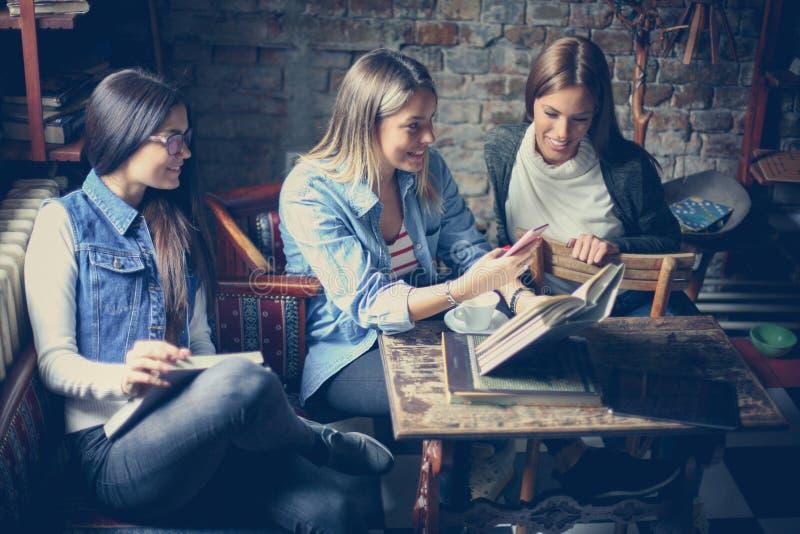 Trzy uczni dziewczyna używa wiszącą ozdobę w bibliotece obraz stock
