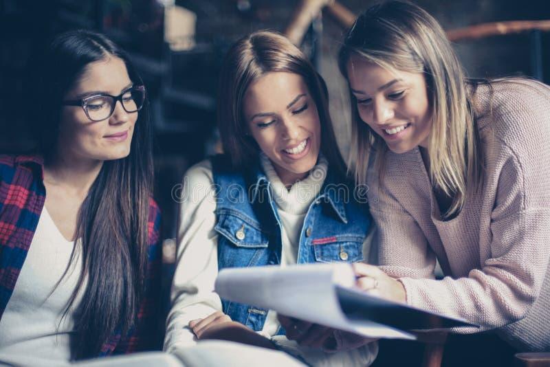 Trzy uczni dziewczyny czytania kartoteka wpólnie indoors obrazy royalty free