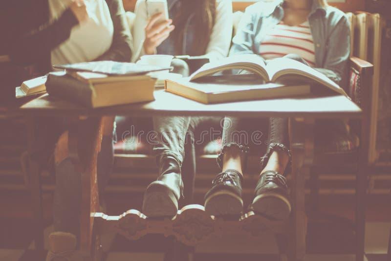 Trzy uczni dziewczyny młody obsiadanie w bibliotece z bliska obraz stock