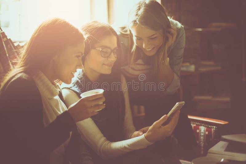 Trzy uczni rozochocona dziewczyna w kawiarni używać mądrze telefon z bliska zdjęcia stock