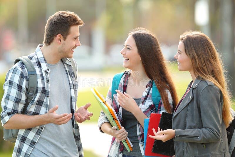 Trzy ucznia opowiadają w ulicie obraz stock