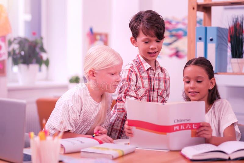 Trzy ucznia patrzeje ciekawą część workbook fotografia royalty free