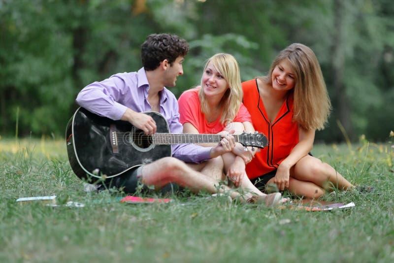 Trzy ucznia z gitary obsiadaniem na trawie w miasto parku obrazy royalty free