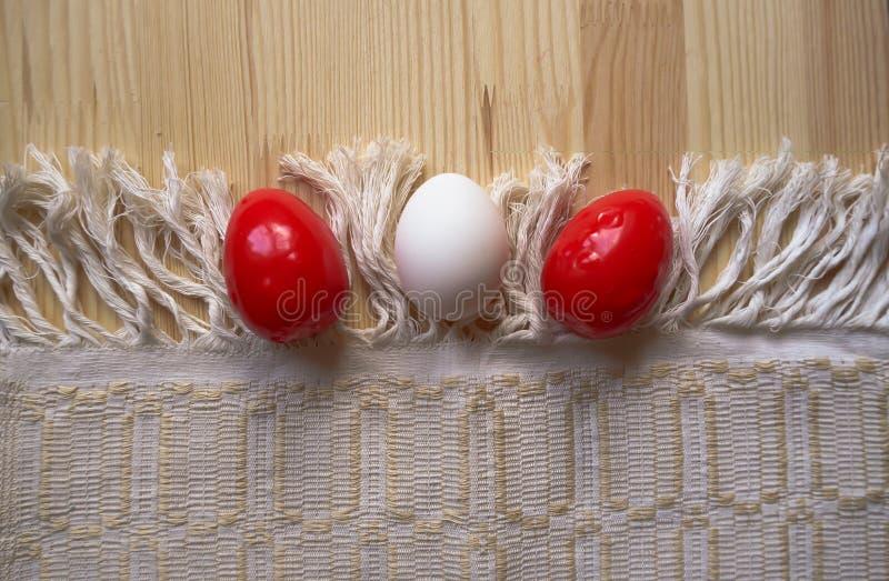 Trzy Wielkanocnego jajka czerwony i biały kolor na drewnianym tle z tablecloth Wieśniaka styl obraz royalty free