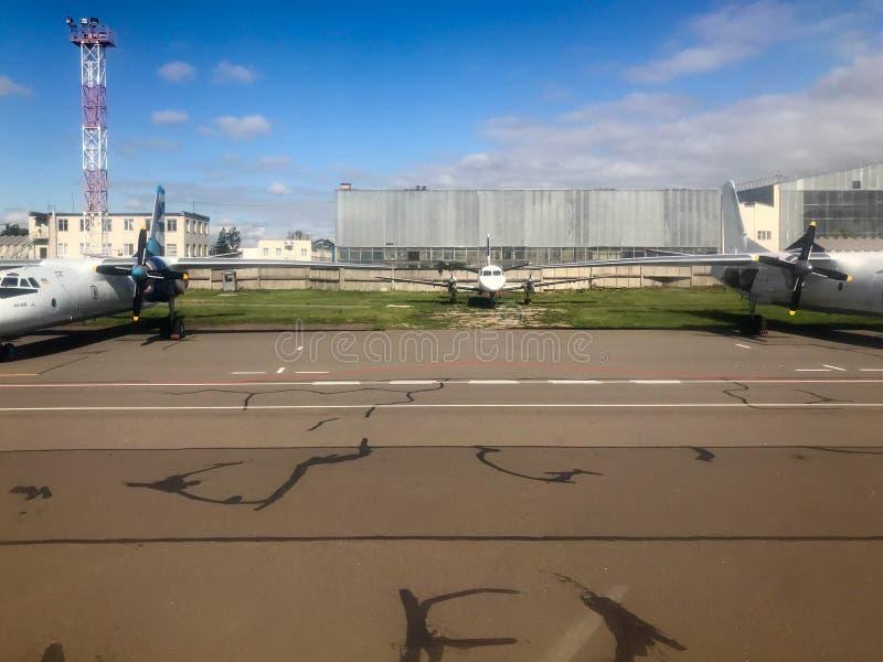 Trzy wielki biały potężny post hebluje z turbina, skrzydła i śruby parkują blisko samolotów hangarów na pasie startowym obraz stock