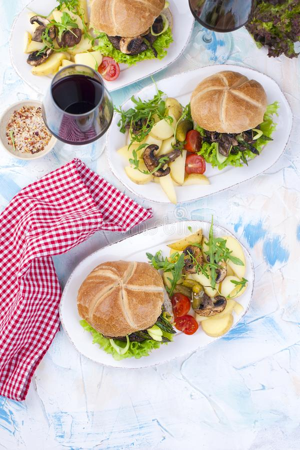 Trzy wielkiego hamburgeru z sałatką i grulami czerwone wino szkła smaczny obiad Szybkie Żarcie Tekst, obrazy royalty free