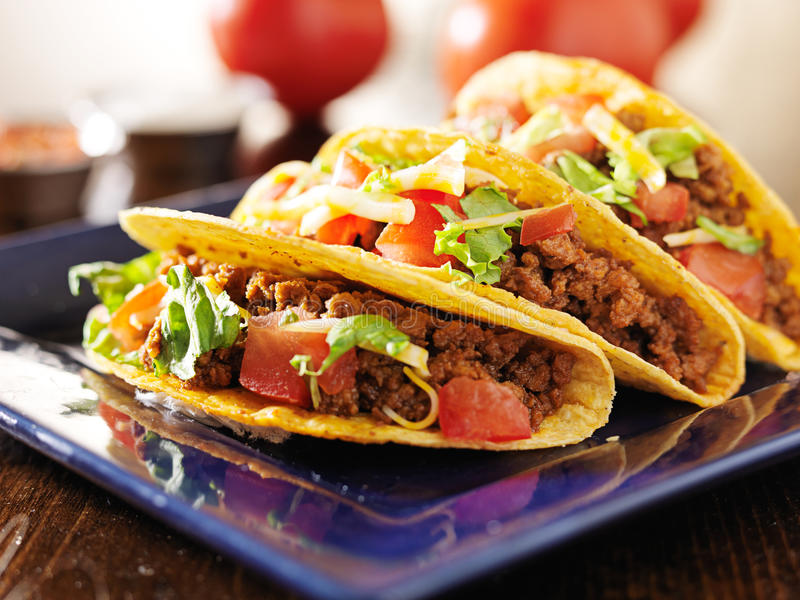 Trzy wołowiny tacos z serem, sałatą i pomidorami, zdjęcia stock