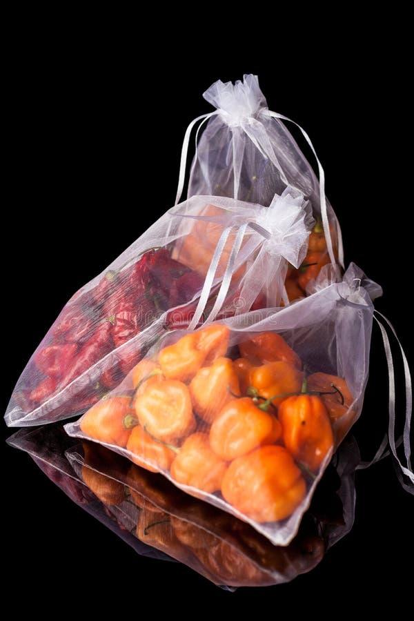 Trzy worka z pomarańczowymi i czerwonymi pieprzami obraz stock