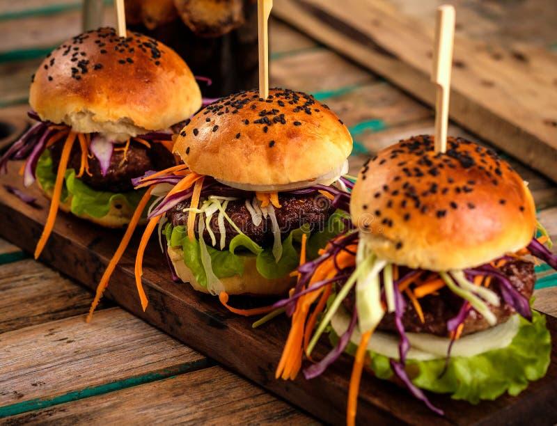 Trzy wyśmienicie świeżego domowej roboty hamburgeru na drewnianym stole fotografia stock
