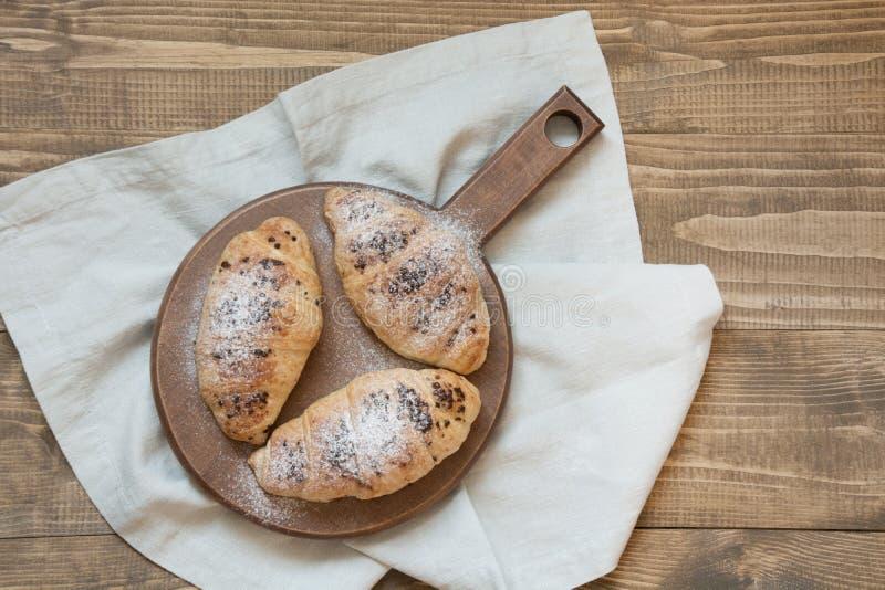 Trzy wyśmienicie świeżo piec czekoladowego croissants na tnącej desce Odgórny widok fotografia royalty free