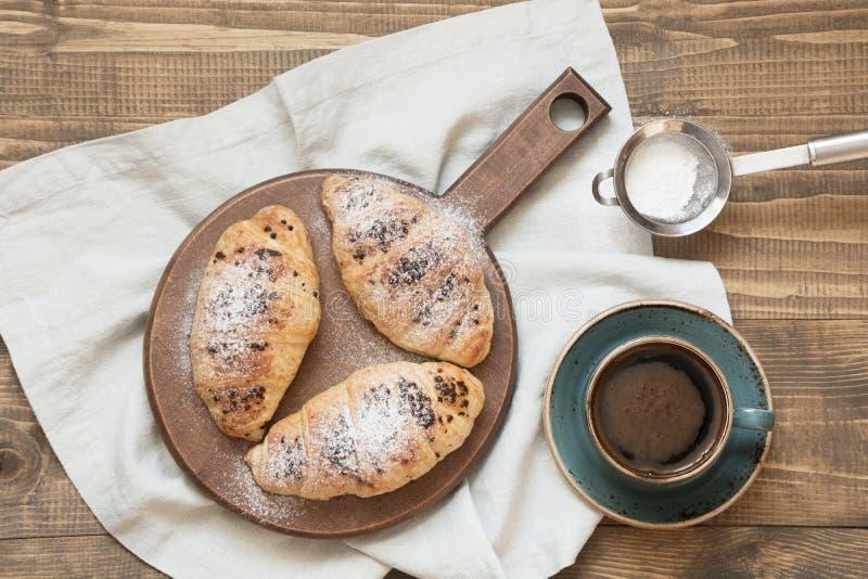 Trzy wyśmienicie świeżo piec czekoladowej filiżanki kawy na tnącej desce i croissants Odgórny widok śniadaniowy kawowy pojęcia fi zdjęcia royalty free