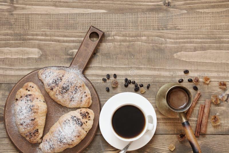 Trzy wyśmienicie świeżo piec filiżanki kawy na drewnianej desce i croissants Odgórny widok śniadanie fotografia stock