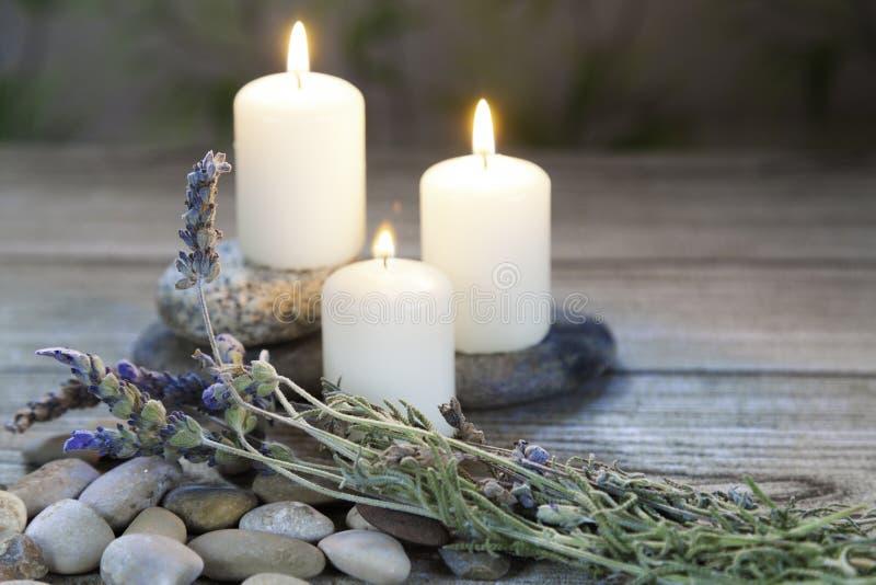 Trzy zaświecali świeczki z lawendą na drewnianym stole i ziołowym tle obraz royalty free