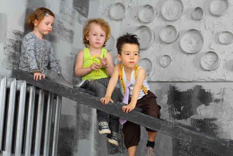 Trzy zanudzającego dziecka siedzi na schodkach obraz stock