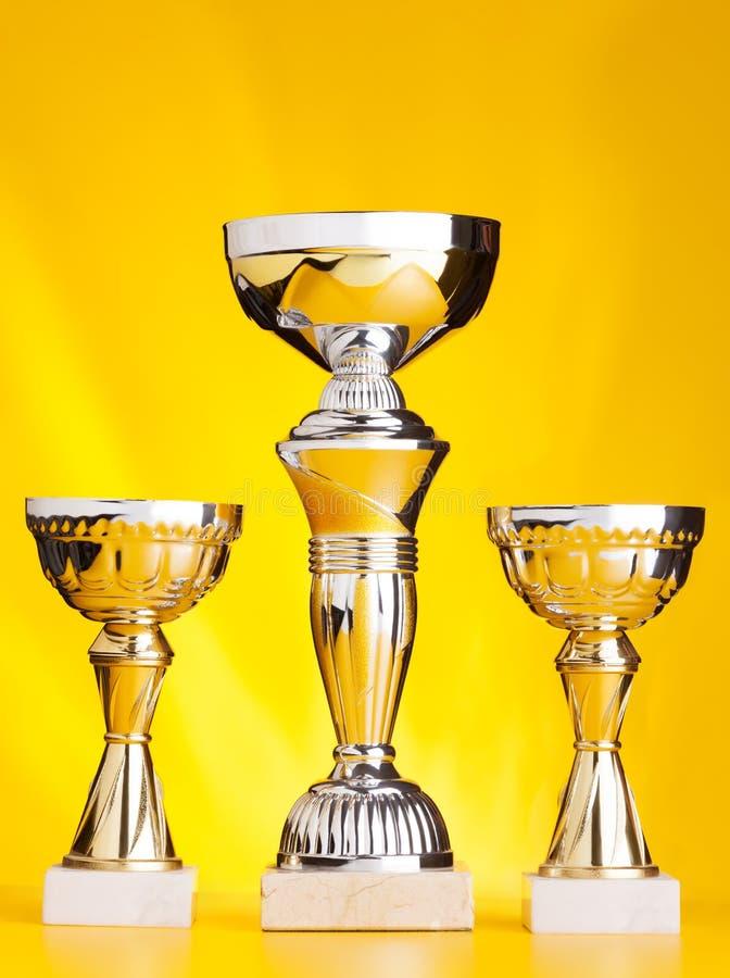 Trzy zwycięzca filiżanki pucharu nagrody na złocistym tle zdjęcie royalty free
