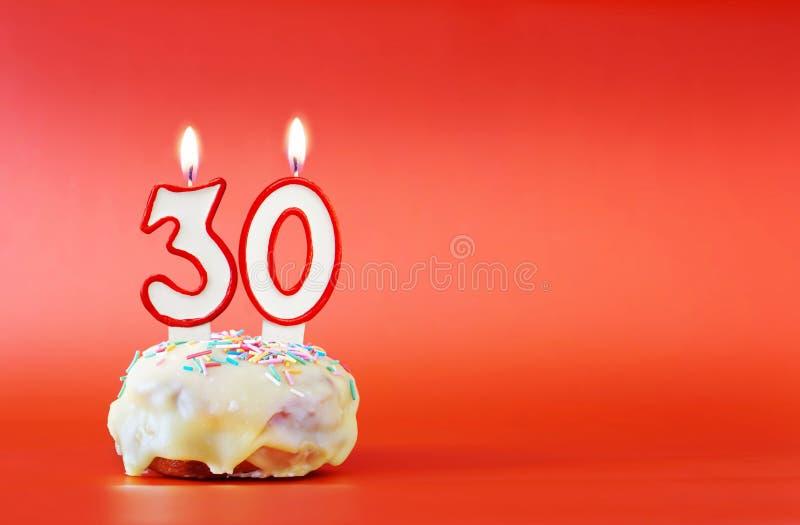 Trzydzieści rok urodzinowych Babeczka z białą płonącą świeczką w postaci liczby 30 zdjęcie royalty free