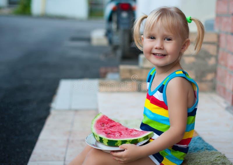 Trzyletni mały Europejski dziewczyny blondynki łasowania arbuz fotografia stock