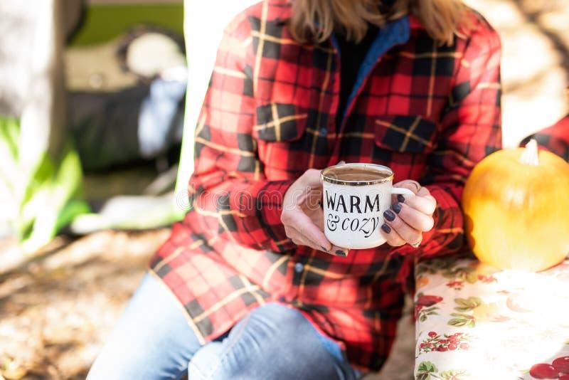 Trzymać kubek gorąca czekolada przy campsite w spadku zdjęcia royalty free