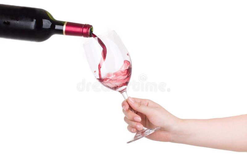Trzymający filiżankę czerwone wino nalewa odosobnionego na bielu obrazy royalty free