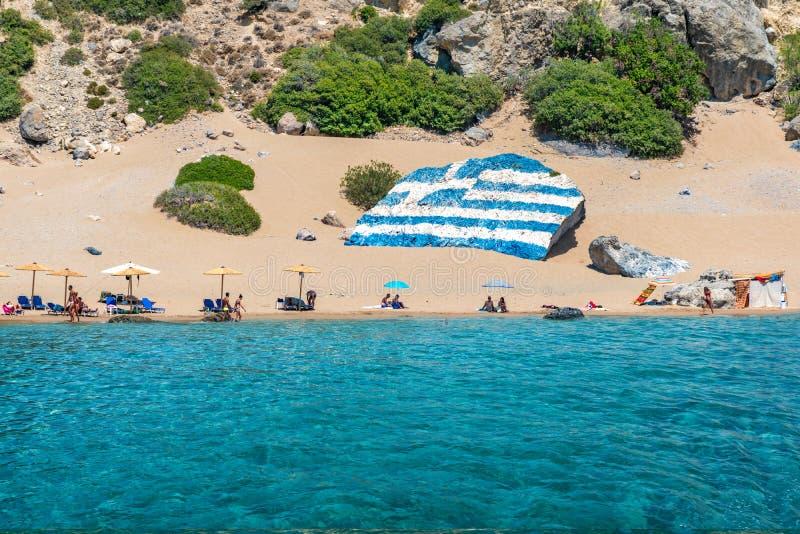 Tsambikastrand met gouden zand met grote Griekse die vlag op r wordt geschilderd stock foto