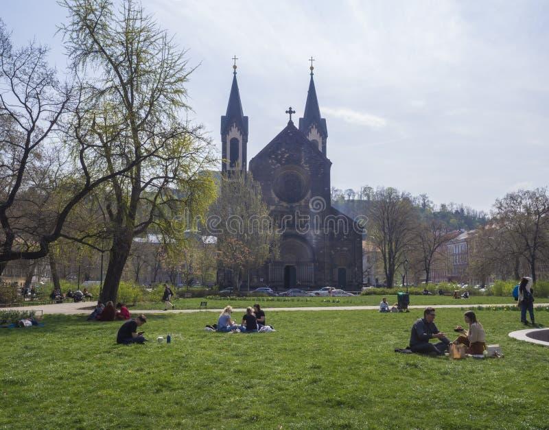 Tschechische Republik, Prag, am 13. April 2019: Gruppe von Personen, die auf üppigem grünem Gras sich entspannt und an Vorfrüh lizenzfreie stockbilder