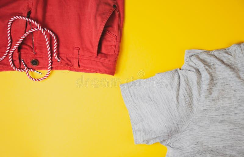 Tshirt cinzento e short vermelho no fundo amarelo, vista da parte superior imagem de stock